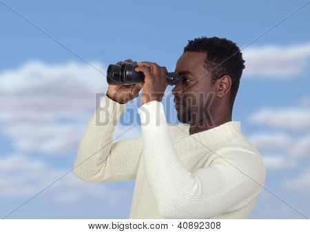 Attractive african man looking through binoculars with a blue sky of background
