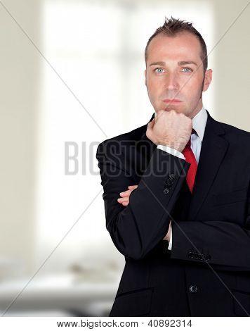 Empresario pensativo en la oficina con un un fondo brillante