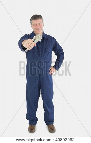 Full length portrait of mature mechanic holding pliers over white background