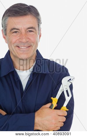 Portrait of happy mechanic with arms crossed holding  pliers over white background