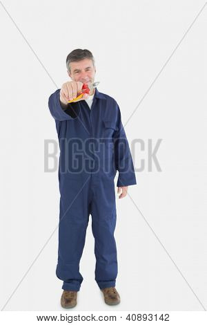 Portrait of happy technician holding pliers against white background