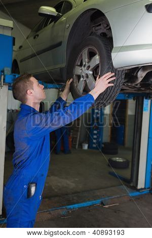 Side view of male mechanic examining car tire in workshop