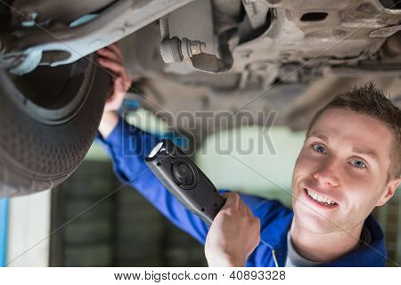 Close-up portrait of male mechanic with flashlight examining tire