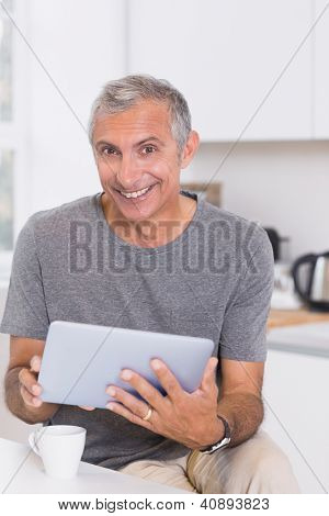 Smiling man using his digital tablet in the kitchen