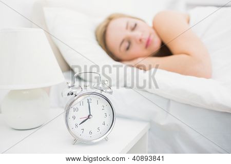 Young woman sleeping in bed with focus on alarm clock at home