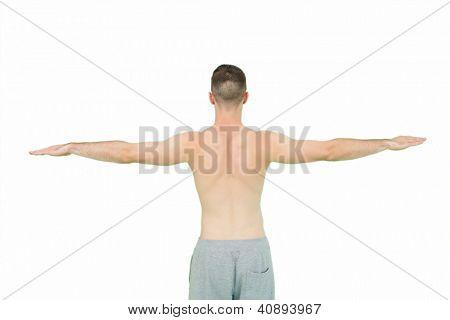 Rear view of young shirtless man standing with arms outstretched over white background
