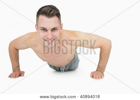 Portrait of happy shirtless young man doing push ups over white background