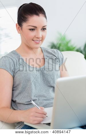 Smiling woman sitting on the couch in a living room and holding a pen while using the laptop