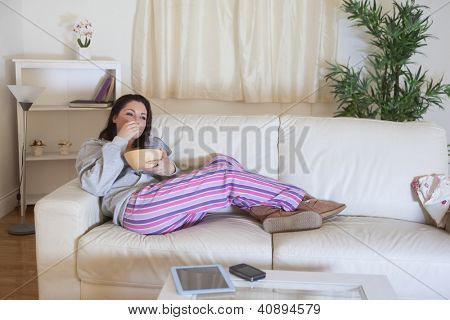 Young relaxed woman in nightwear sitting on couch with bowl at home