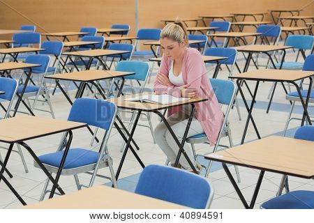 Blonde student studying at desk in empty exam hall in a college