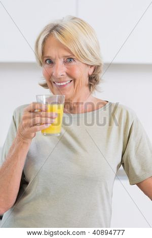Smiling woman drinking orange juice in the kitchen