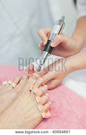 Close-up of hands removing callus at feet