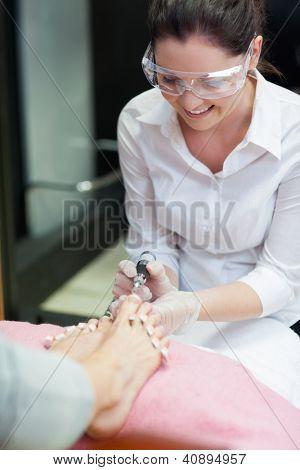 Nail technician removing callus at feet in nail salon