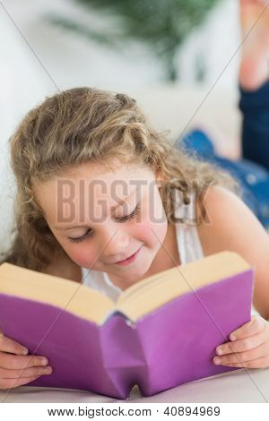 Smiling girl resting on the sofa with book