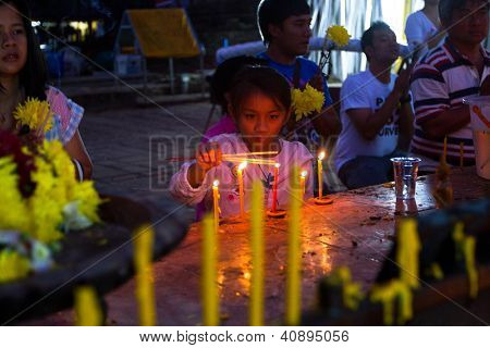 CHIANGMAI,THAILAND - DEC 31: Unidentified child in a Buddhist temple during the New Year celebrations, Dec 31, 2012 in Chiangmai, Thailand. Thai official calendar now is 2555 year.