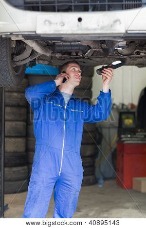 Young male mechanic on call as he examines under car