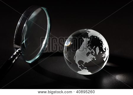 Earth with magnifying glass and light beam