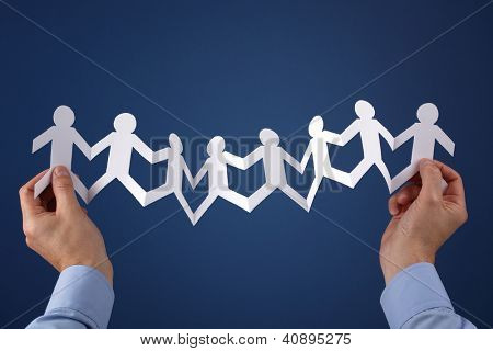 Teamwork concept with paper chain group of people holding hands held over blue background