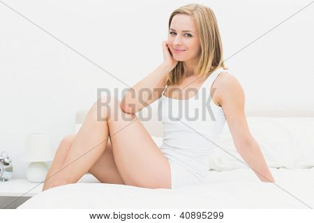 Portrait of smiling young woman sitting in bed at home