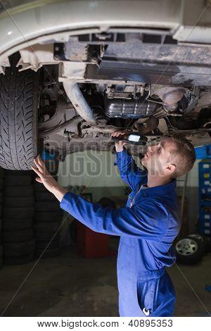 Male mechanic examining car using flashlight in garage