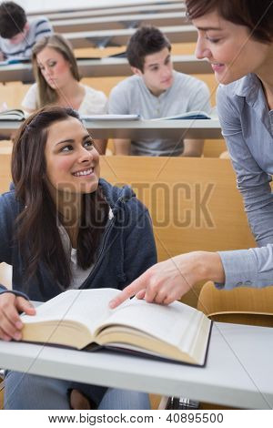 Lecturer explainging to student in lecture hall with large book
