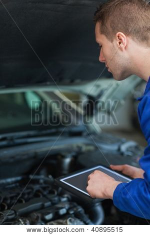 Male mechanic using digital tablet while examining car engine