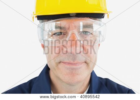 Close-up portrait of mechanic wearing hardhat and protective glasses over white background