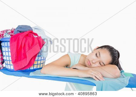 Woman sleeping on an ironing board near a basket full of laundry in a white background