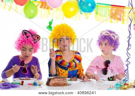 Children happy birthday party eating chocolate cake with clown wigs