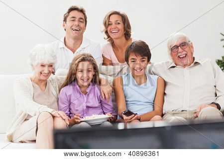 Extended family watching tv together on the couch