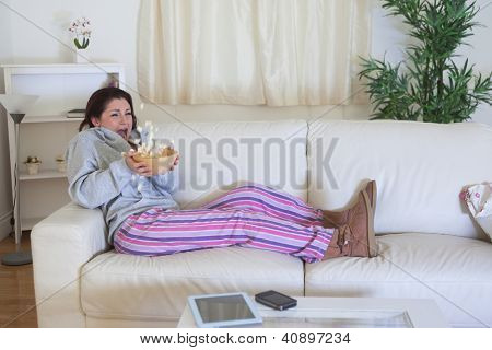 Scared young woman throwing popcorn while watching film on couch at home