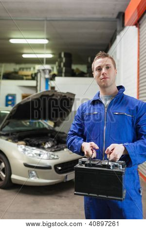 Portrait of confident auto mechanic with car battery in workshop