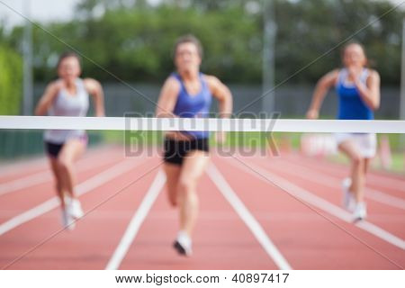 Female athletes racing towards finish line at track field