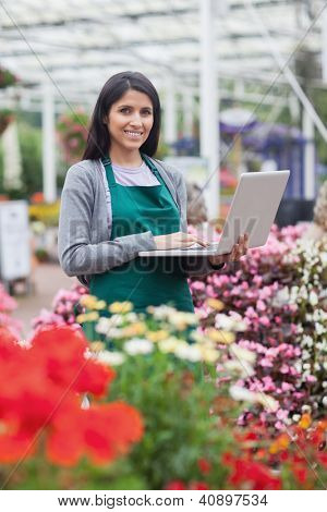 Brunette typing on the laptop in the garden centre while smiling