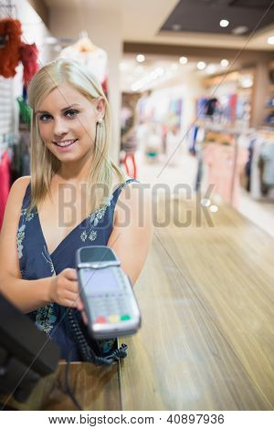Woman showing credit card machine in clothes store