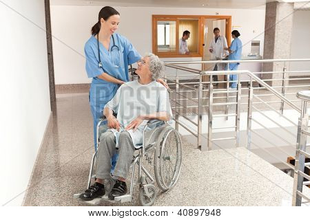 Nurse watching over old women sitting in wheelchair in hallway