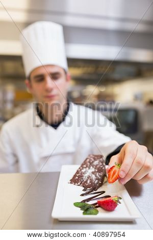 Chef putting a strawberry with the cake on plate in the kitchen