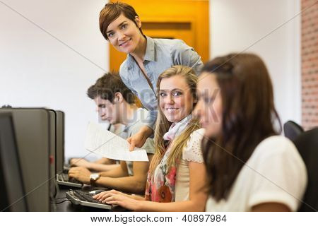 Student and teacher smiling at the computer room of the university