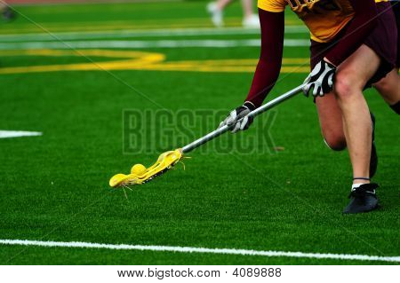 Lacrosse player scooping up the ball on a turf field.