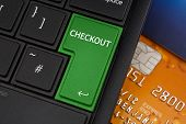 picture of qwerty  - Checkout Enter Key on a modern laptop qwerty keyboard with bank smart card underneath to represent online shopping - JPG