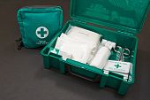 stock photo of emergency treatment  - A green standard First aid kit used to provide urgent emergency treatment at school work or in the home - JPG