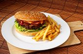 stock photo of bap  - Bacon cheeseburger with a homemade beef patty on a bed of lettuce with a side of fries - JPG