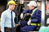 foto of forklift driver  - Young forklift driver communicating with supervisor at warehouse - JPG