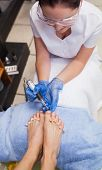 image of callus  - Nail technician removing callus at feet in nail salon - JPG