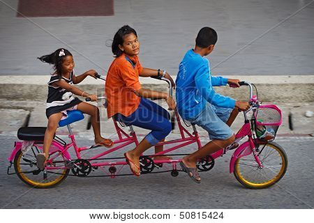 Three Childred On Tandem Bicycle On A Road