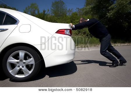 Businessman Pushing A Car