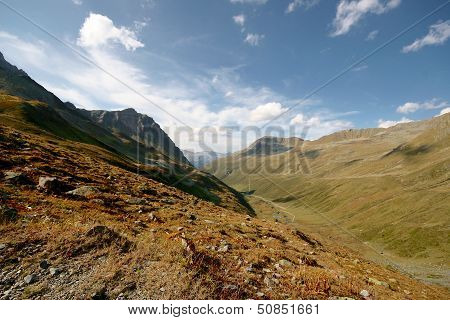 Grass Alpine Meadow Surrounded By High Mountains In Swiss Alps, Switzerland.