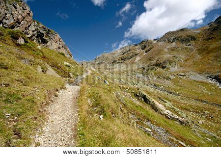 Rocky Trail Leading To Valley Surrounded By High Mountains In Swiss Alps, Switzerland.