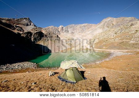 Tent At Bivouac At A Rest Place By The Lake In Alp Meadow In Swiss Alps