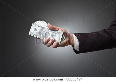 businessman hand holding money on dark background